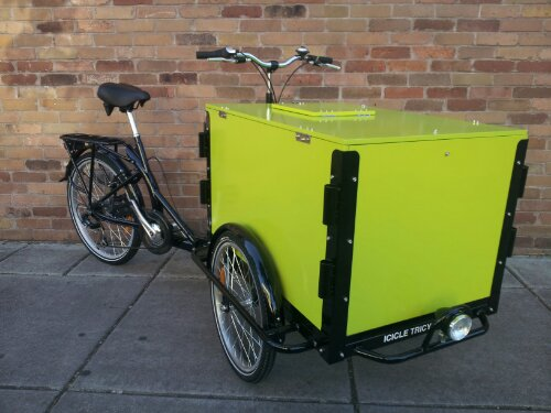 an Icicle Tricycles Custom Cargo Bike with the panels wrapped with green vinyl wrap parked on the sidewalk in front of a brick wall