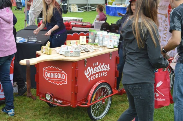 A red Darigold branded marketing Cargo bike with a custom lid shaped like a giant cutting board with a full spread of butter and cheese at a marketing event