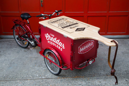 A red Darigold branded marketing Cargo bike with a custom lid shaped like a giant cutting board parked on the sidewalk by a red bay door.