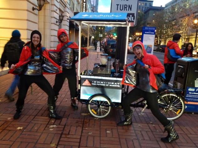 A group of stoked peddlers posing next to their coffee Custom Cargo Bike parked on the sidewalk in a major city
