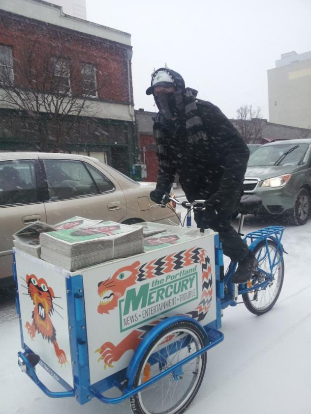 A peddler biking in the snow with an Icicle Tricycles Newspaper Delivery Bike branded for the Portland Mercury