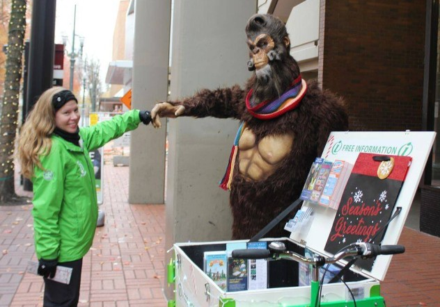 a librarian fist bumping big foot next to a Library Book delivery Bike and Mobile Information Kiosk