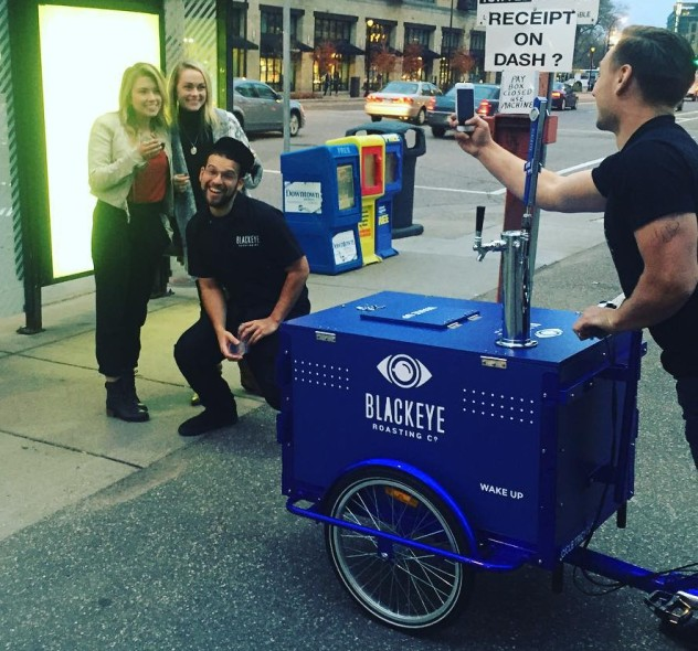 A group of young people smiling in front of a cold brew coffee tap ice cream bike / trike with custom branding in new york city