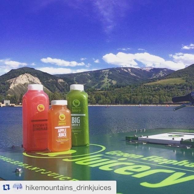 Three bottles of juice on the lid of an ice cream bike in the foreground and a beautiful landscape shot of a lake and mountains in the background