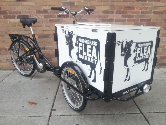an Icicle Tricycles Advertising delivery Bike branded for a flea market parked on the sidewalk in front of a brick wall.