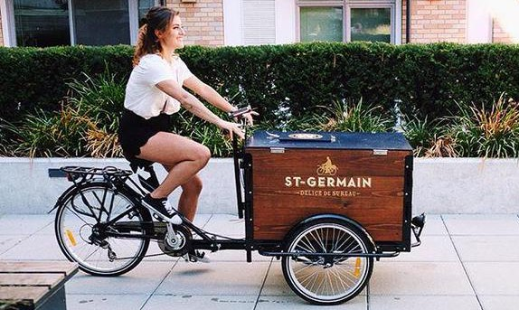 A Peddler pedaling a St-germain branded custom cedar cargo box delivery bike down the sidewalk on a sunnuy day