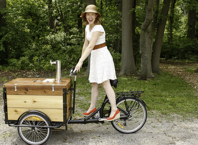 A woman in a white sun dress riding an Icicle Tricycles Cold Brew Coffee Cedar wood Cargo Bike down dirt road in the woods