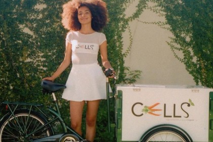 an icicle tricycles food bike branded for cells sprouted raw vegan foods and a person in front of a wall of vines