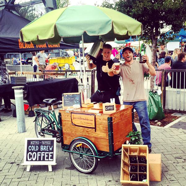 two happy baristas with a custom cedar box cold brew coffee bike at an event