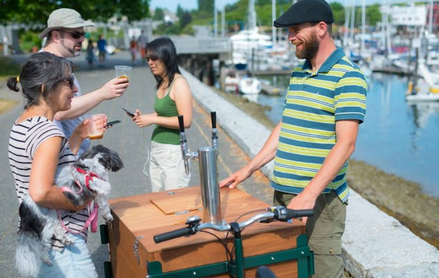 A man smiling at a woman holding a dog standing above a cedar wood cargo box cold brew coffee bike / trike at a marina.