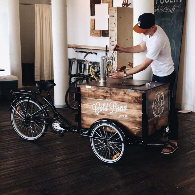 Man in t shirt and ball cap pours Cold Brew Coffee from the tap on the coffee bike box