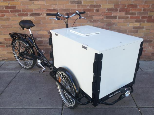 A standard Icicle Tricycle commercial cargo Ice Cream bike with a black frame parked on the side walk by a brick wall
