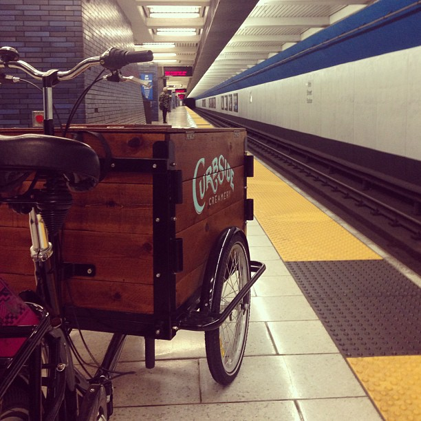 Icicle Tricycles Front load custom cedar wood box branded Ice Cream Bike Cart in a BART station waiting for the train