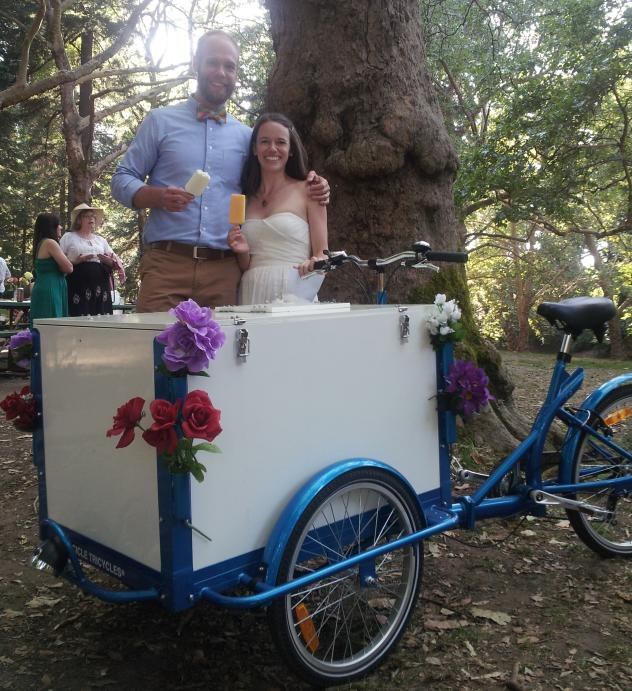 A couple eating Popsicles behind blue framed Icicle Tricycles front load Ice Cream Bike / Trike standard ice cream bicycle model in the woods