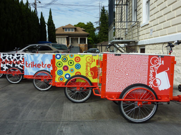 A fleet of Icicle Tricycles marketing custom branded Ice Cream Bikes with red frames in an alley way on a sunny day.