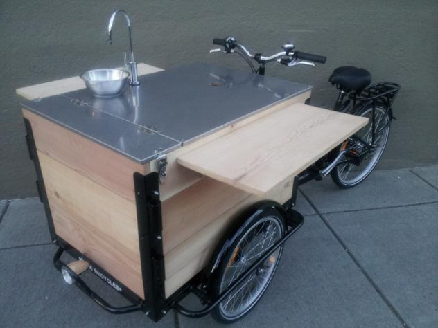 A cedar wood Coffee Bike / Trike with a custom sink installed on the lid and folding shelves on the side.