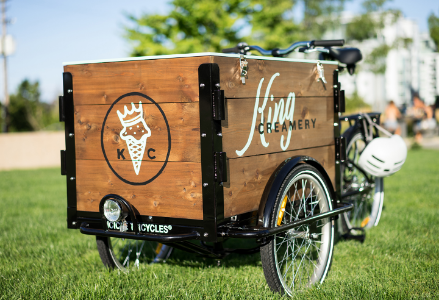 An Icicle Tricycles cedar box ice cream bike / trike in a grassy field on a sunny day branded for King Creamery