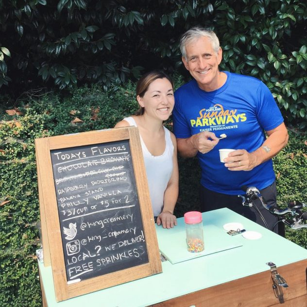 two smiling people with ice cream posing behind a cedar wood front load ice cream food bike at a park