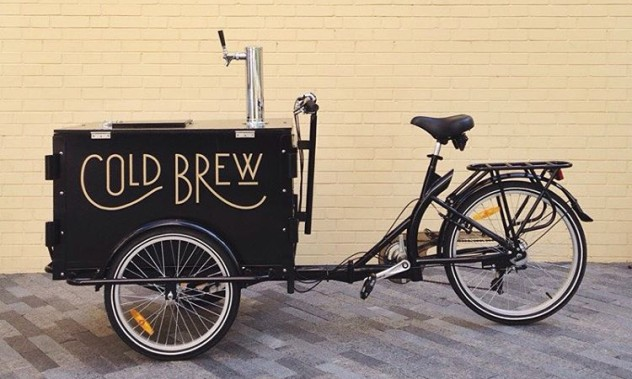 A custom wrap branded cold brew coffee tap ice cream bike / trike in front of a yellow brick wall