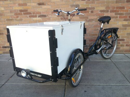 An Icicle Tricycles Used front load cargo box ice cream bike / trike with a black frame parked on the sidewalk in front of a brick wall