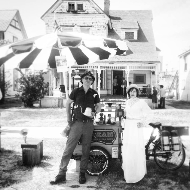 two coffee crafters posing with their Stream Coffee and Teas branded Icicle Tricycles Coffee Cargo Bike on the curb in a neighborhood in black and white