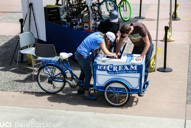 2 People reaching into a branded icicle tricycle ice cream bike with a blue frame at a marketing event