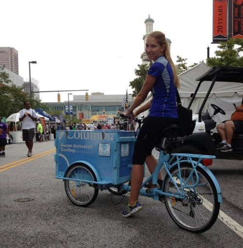 A woman riding an Icicle Tricycles Experiential Marketing Cargo Bike with custom powder coat frame at a street fair