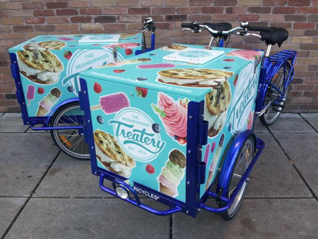 Two Icicle Tricycles Ice Cream Tricycles / Bicycles branded The Treatery parked on the sidewalk in front of a brick wall