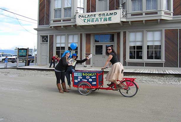 A peddling librarian on an Icicle Tricycles Book Bikes - bikes for book distribution, marketing, and delivery.