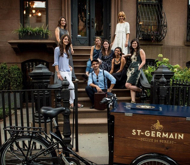 A group of people are posing on a stoop behind a St-Germain Wood Cargo Delivery Bike / Mobile Beverage Cart Designed by Icicle Tricycles