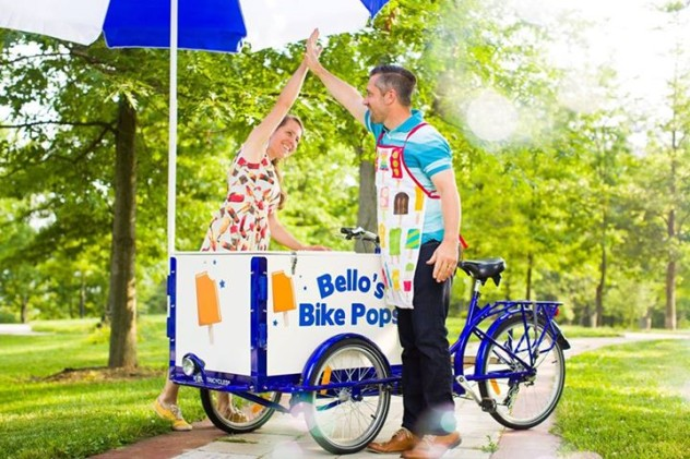two people high fiving over an ice cream bike in a park on a sunny day