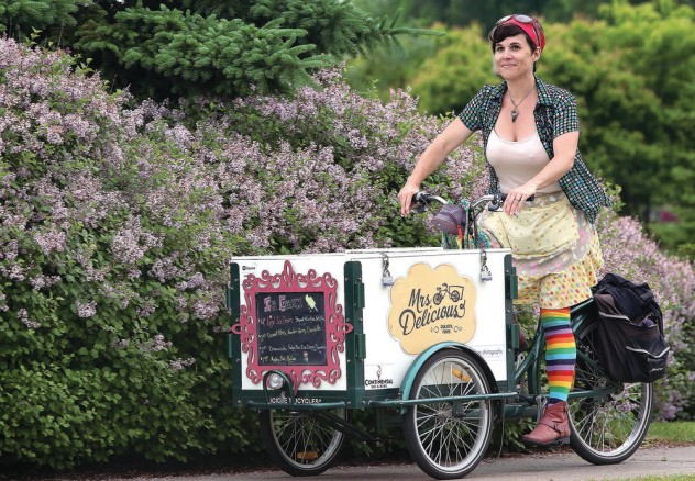 Mrs Delicious riding an ice cream tricycle bike through a park