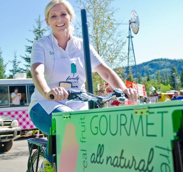 A woman pedaling her family freezed branded icicle tricycles ice cream bicycle / tricycle icicle tricycles at a food cart popup.