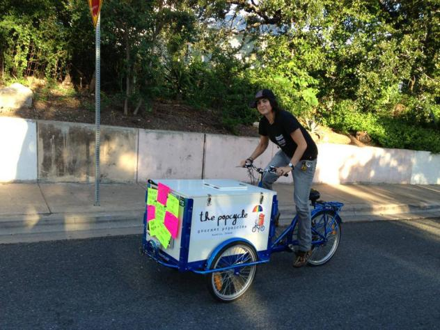 an Ice Cream Bike / Trike By Icicle Tricycles with a blue frame rolling down the street