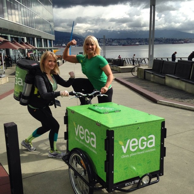 two promoters showing off and posing with there Vega branded front load food trike with a black frame at a marina