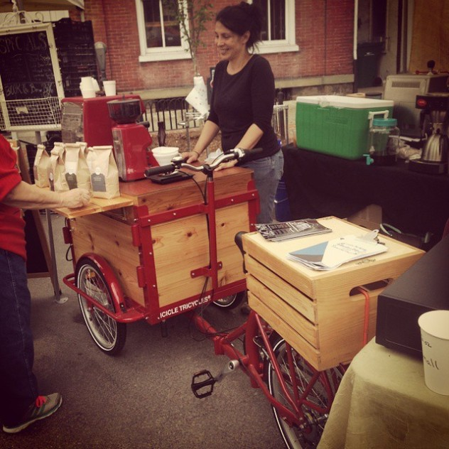 a woman selling bags of coffee in the street from her icicle Tricycles brand custom cedar wood coffee bike / trike with a red frame and a folding shelf