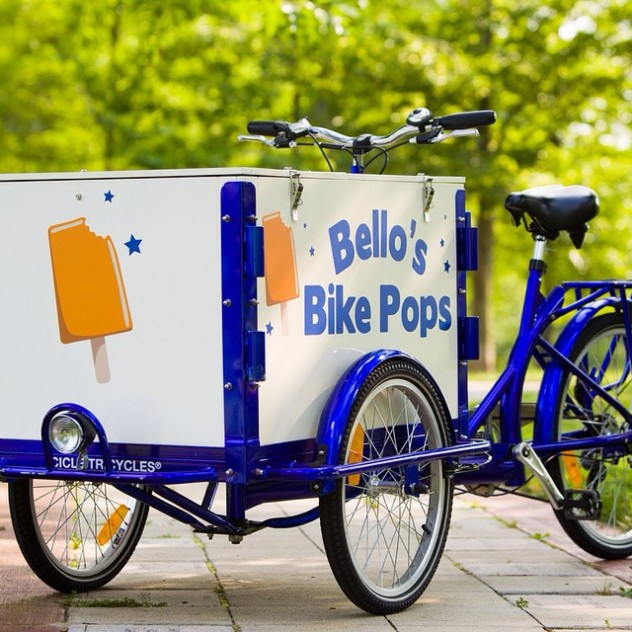 An icicle Tricycles ice cream bike / trike branded for Bello's bike Pops sitting in a park.