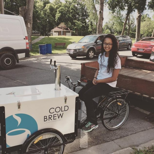 "Smiling barista sits on a ""Cold Brew"" branded coffee bike parked on the street on a sunny day"