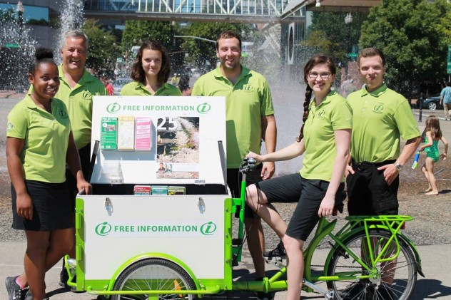 Smiling team of people with mobile information kiosk ice cream bike in front of a fountain.