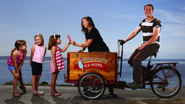 A Cedar wood artisan ice cream bike with a red frame at the ocean. Children are lined up for ice cream.