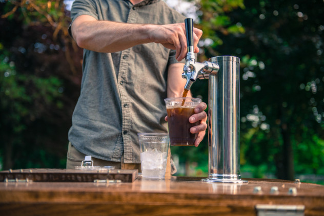 Person pouring cold brew coffee from a tap on a coffee bike cart