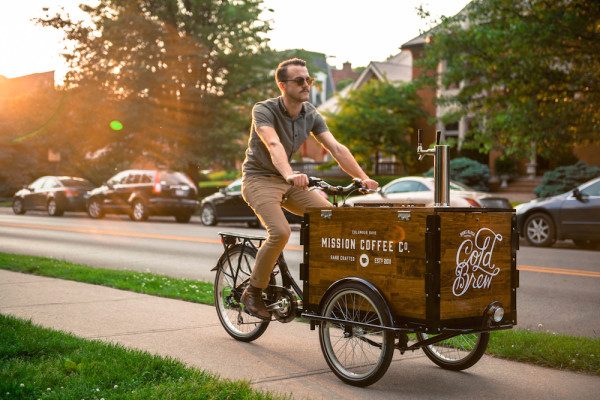 A man riding a cold brew coffee bike / trike down the side walk