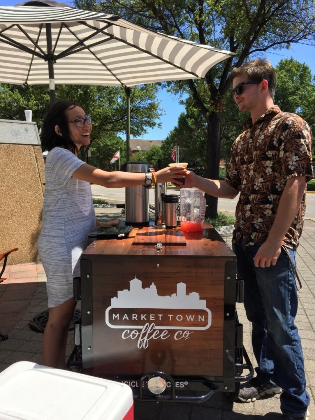 A person being served cold brew coffee from a cold brew coffee bike / trike branded for Market Town Coffee co on a sunny day in a park