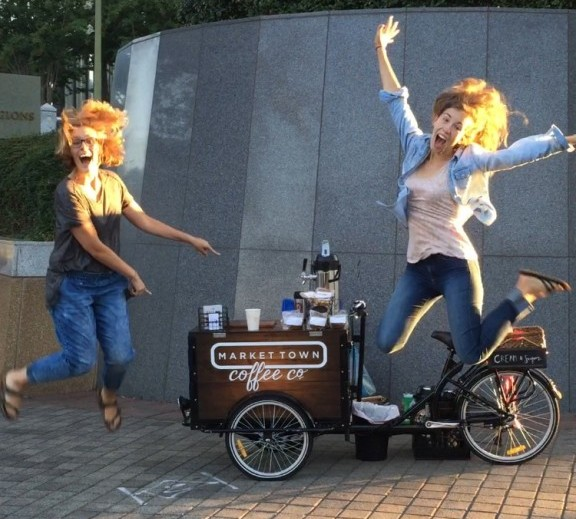 two people jumping in the air with joy and pointing at a custom branded coffee bike cart