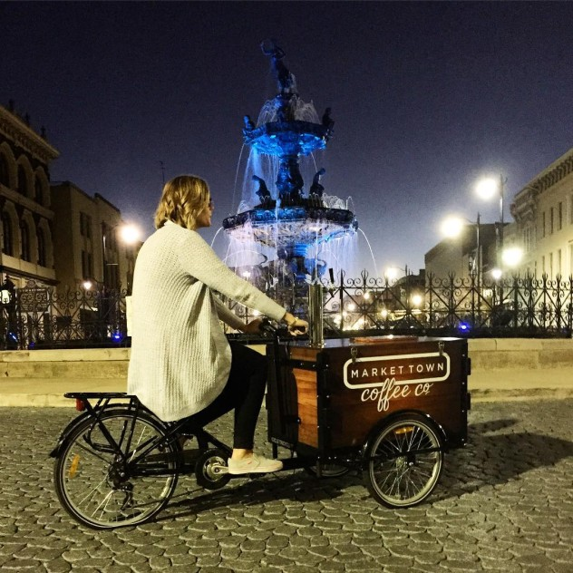 a woman riding a branded cold brew coffee bike / trike on cobble stone by a fountain