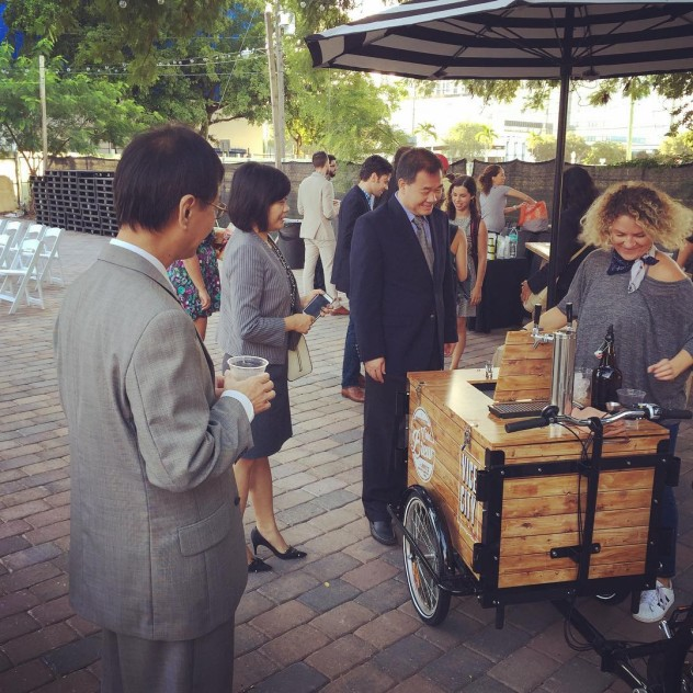 A group of people in suits being served coffee from a branded cold brew tap coffee bike / trike