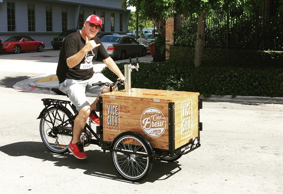 A man waving a shocka while riding a cold brew coffee bike cart