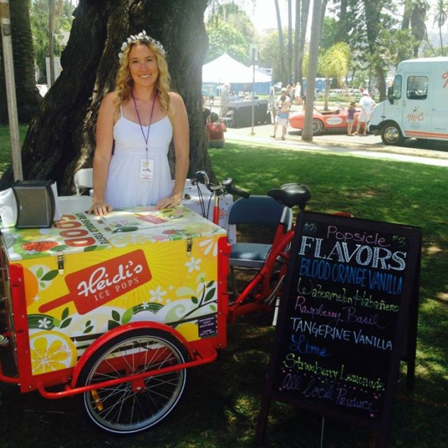 Woman posing behind an ice cream cart branded for Heidi's at a popup event