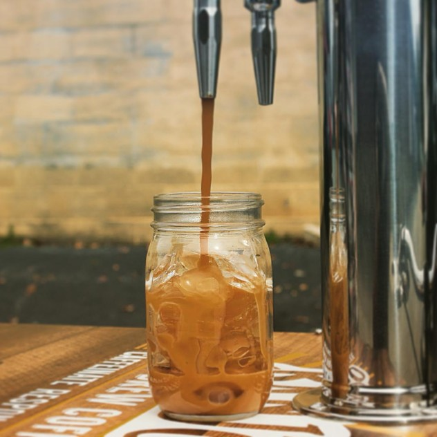 nitro cold brew coffee pouring straight from the tap on the lid of a coffee cart