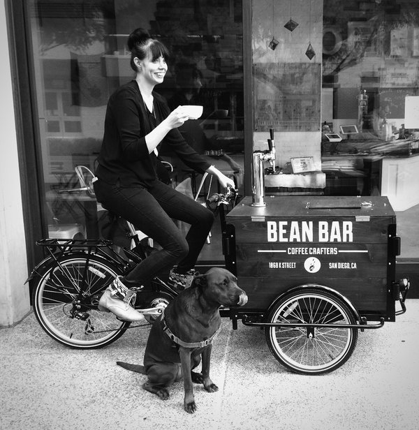 a woman sitting on a cold brew coffee tricycle ice cream bike and a dog sitting on the ground.